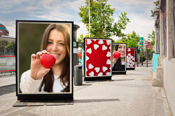 Love billboards, photographs of a woman with red heart, at city