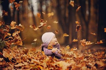 Маленькая девочка играет с листьями в лесу