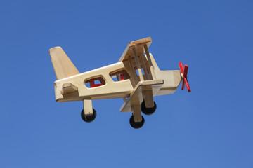 Avión de madera volando con cielo azul - Vista lateral