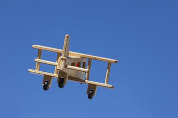 Avión de madera volando con cielo azul - Alejándose