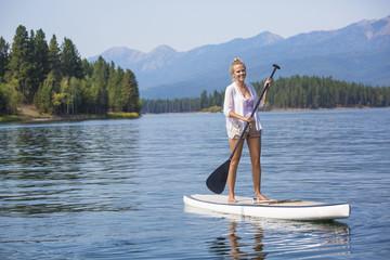 Beautiful woman paddleboarding on scenic mountain lake
