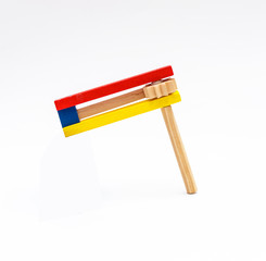 A child's hand holding Colorful wooden noisemaker Purim holiday