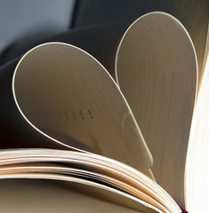 Book pages folded into heart shape. Book card for Valentine's day. Love