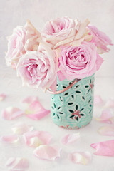 Beautiful pink roses in a blue ceramic vase on a light background.