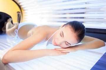 Attractive woman is getting sunbathing beauty treatment