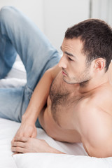 Attractive young guy is resting in bedroom