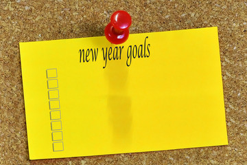 new year goals  word on notepaper with cork background