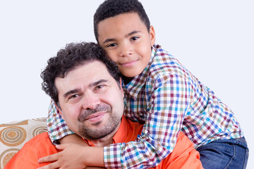 Cheerful child hugging his father on father's day