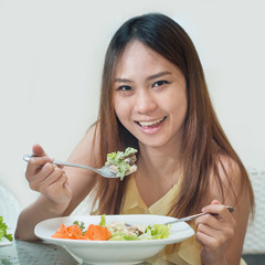 Close-up Of Beautiful Asia Woman suntan skin Eating Salad At Hom