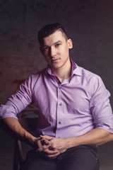 Fashion portrait of young man in lilac shirt looking at camera