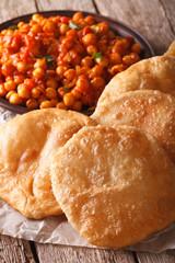 Indian bread puri and chana masala macro. Vertical