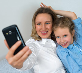 Mother and daughter taking selfie with mobile phone.