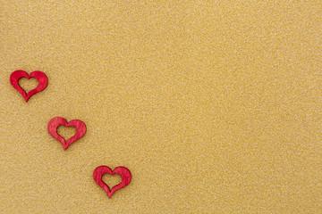 drei rote Herzen auf goldenem Hintergrund