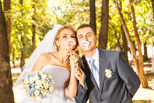 Wedding couple posing with stick lips, mask