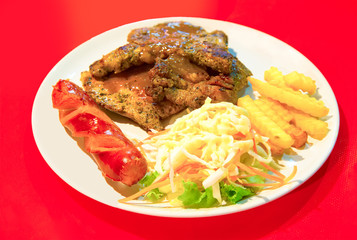 Grilled Porkchop Steak with salad, Smoked Sausage and French Fri