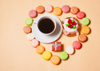 French macaroons, cup of coffee, gift box  and cake