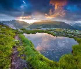 Foto auf AluDibond Reflexion Dramatic sky reflected in small lake in Swiss Alps