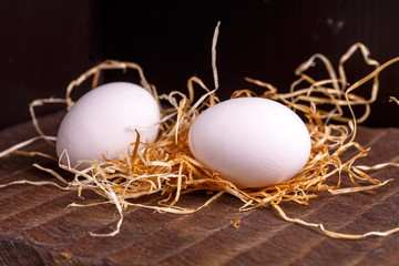 Two white chicken eggs lying on the dark Board on the dry grass.