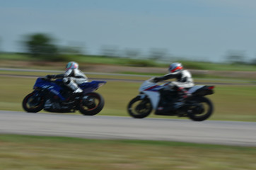 Blurred athletes practicing racing motorcycles on the race track