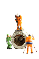 Miniature construction workers plumbing valve / Isolated miniature scale model construction workers with a plumbing valve