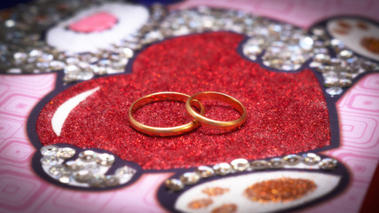 Two rings on a red glittery heart
