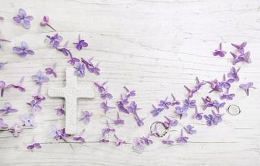 Weißes Kreuz mit Flieder Blüten auf Holz als Hintergrund für eine Trauerkarte