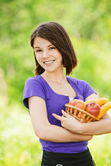 portrait of young happy woman holding basket with juicy fruits