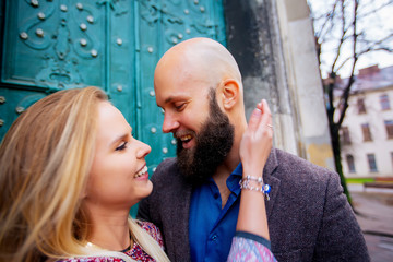 Young couple in love, hugging on the street. Selective focus. bald guy with a beard