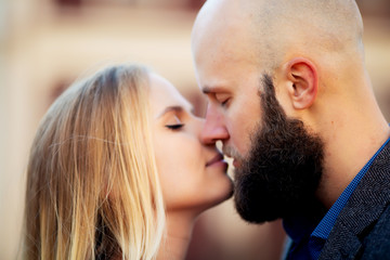 happy couple in love with each other,One beautiful stylish couple of young woman and senior man with long black beard   embracing close to each other outdoor in autumn street on stairs sunny day
