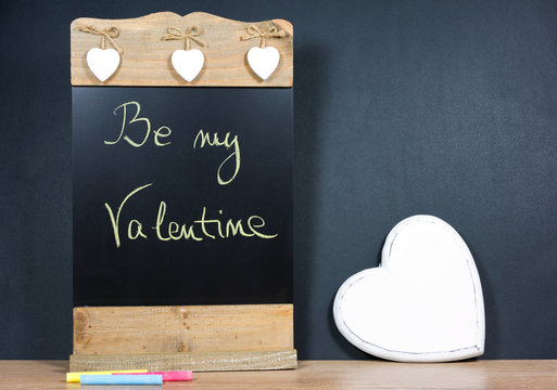 Empty wooden chalkboard and white hearts on black background