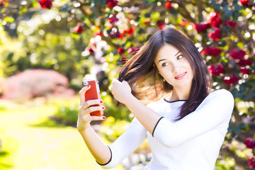 Beautiful girl posing for a selfie with her smart phone