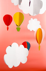 Paper clouds and airship on pink background