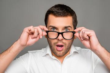 Surprised man touching glasses