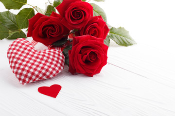 Hearts and a bouquet of red roses on wooden board,