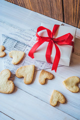 White box with red ribbon, the envelope, cookies in the shape of heart, red candles. Romantic gift on Valentine's Day on wooden background.
