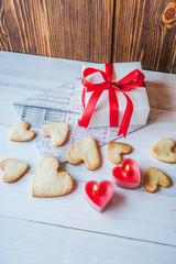 White box with red ribbon, the envelope, meringue, cookies in the shape of heart, red candles. Romantic gift on Valentine's Day on wooden background.