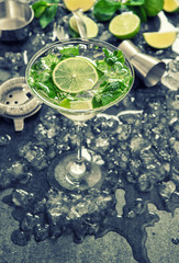 Cocktail with lime, mint, ice. Bar drink accessories. Vintage st