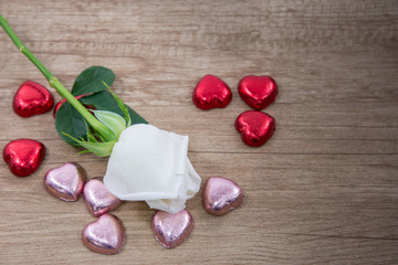 A White rose with chocolate on the wooden floor