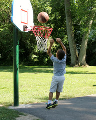 Child Playing Basketball Outdoors
