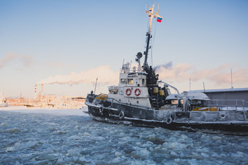 The Icebreaker ship trapped in ice tries to break and leave the arctic bay between the glaciers