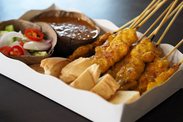 Pork Satay with peanut sauce and cucumber salad on white paper food tray