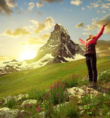 Girl on meadow, in the background mount Matterhorn - Swiss Alps, Europe
