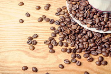Fresh coffee beans on a wooden background for the preparation of