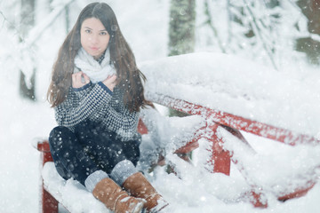 Adult girl in a sweater in the winter snowy forest