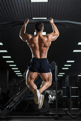 Muscle athlete man in gym making elevations. Bodybuilder training pull ups on horizontal bar
