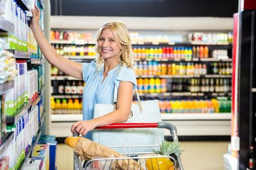 Smiling woman taking food from shelf