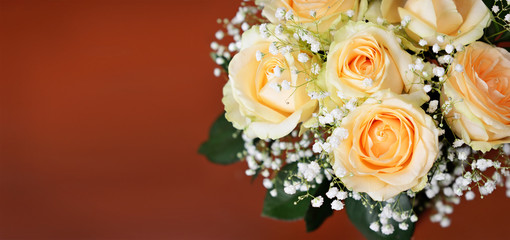 Bouquet of peach rose flowers on brown background