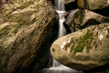 great wonders of nature - river waterfall surrounded by big rocks in forest