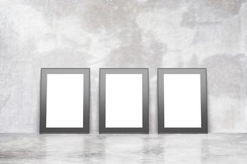 Blank picture frames on concrete floor in empty loft rooml, mock