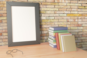 Blank picture frame standing on a wooden table with books, mock